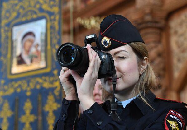 Сотрудник полиции фотографирует во время Божественной литургии в кафедральном соборе Успения Пресвятой Богородицы в Астрахане