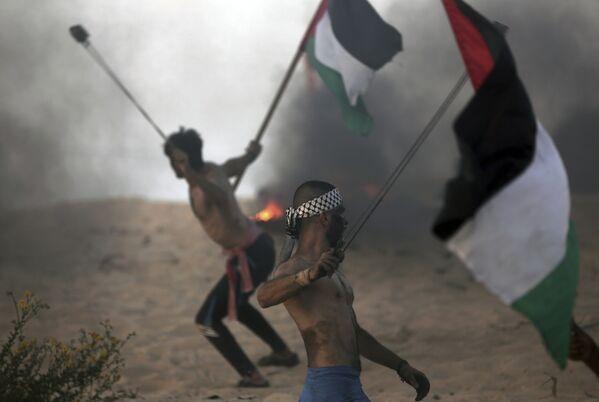 Палестинские демонстранты бросают камни в израильских военных на акции протеста возле границы вблизи Бейт-Лахии