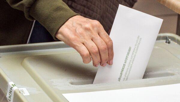 Избиратель опускает бюллетень в урну на выборах президента Грузии на одном из избирательных участков в Тбилиси. 28 октября 2018