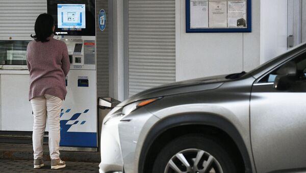 Женщина у терминала оплаты на автозаправочной станции Газпромнефть в Москве. Архивное фото