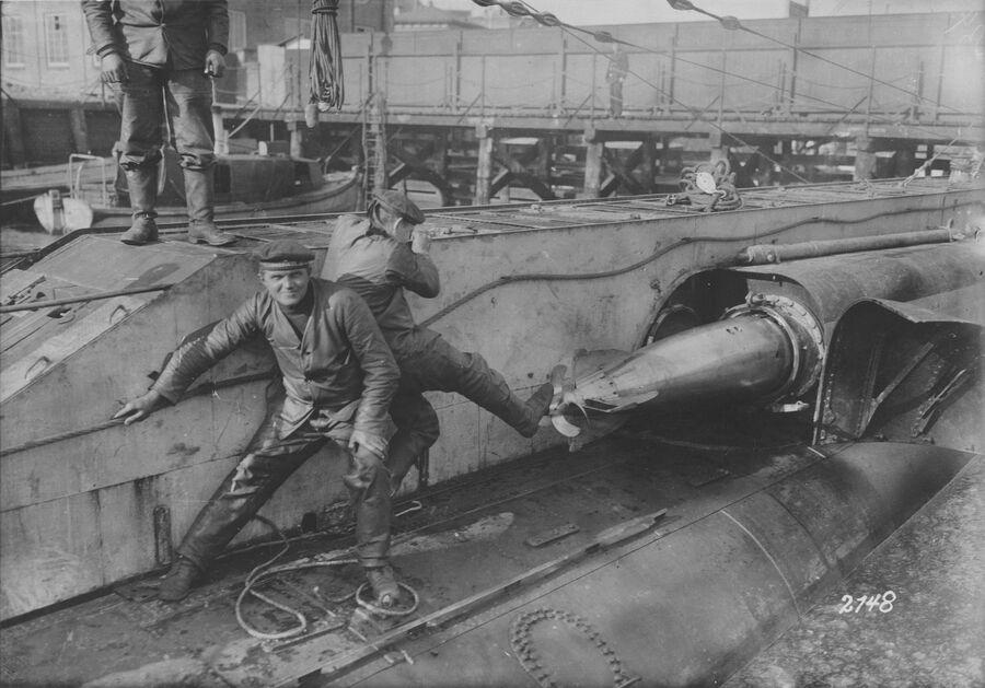 Германские моряки заряжают торпедами торпедные аппараты на подводной лодке. Первая мировая война