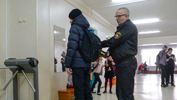 Сотрудник службы безопасности проверяет ученика в средней общеобразовательной школе