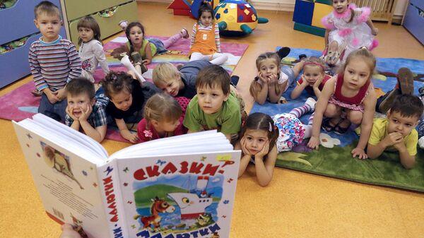 Воспитатель читает детям сказку в комнате отдыха детского сада. Архивное фото
