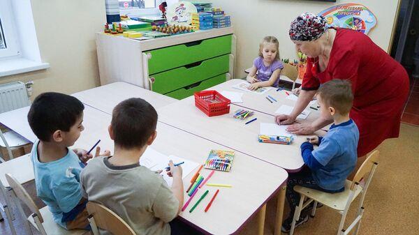 Дети и воспитательница на занятиях в детском саду