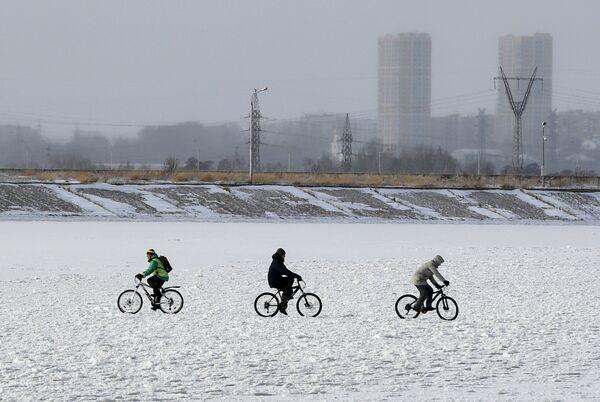 Люди гуляют на льду замерзшего водохранилища Новосибирской ГЭС