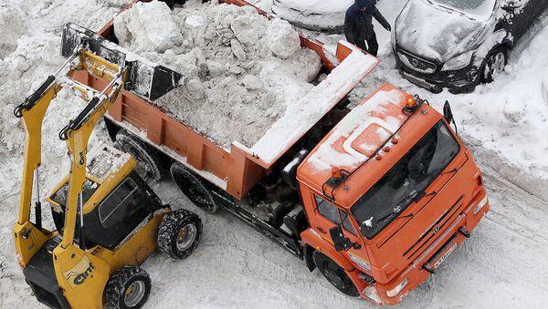 Погрузка снега в кузов грузового автомобиля. Архивное фото