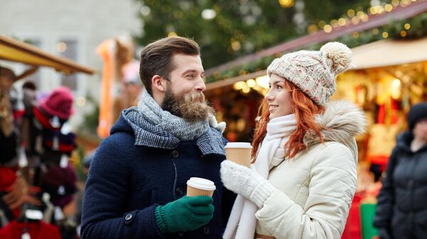 Счастливая пара пьет кофе на улице