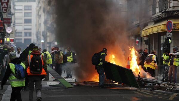 Демонстранты подожгли уличные барьеры во время акции Желтые жилеты в Париже. 24 ноября 2018