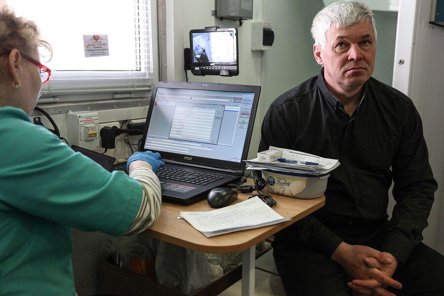 Мужчина проходит флюорографию в передвижном мобильном диагностическом комплексе. Архивное фото