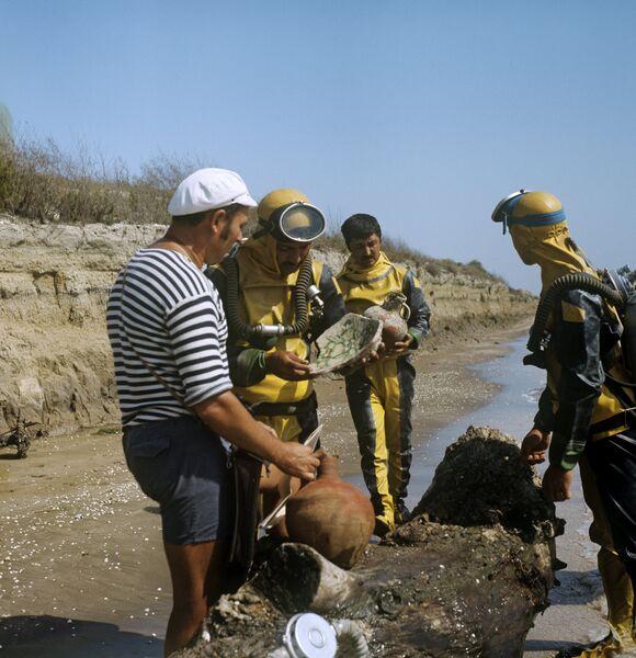 Начальник экспедиции Каспийская Атлантида Виктор Квачидзе (слева) с коллегами рассматривает находки, поднятые со дня моря.