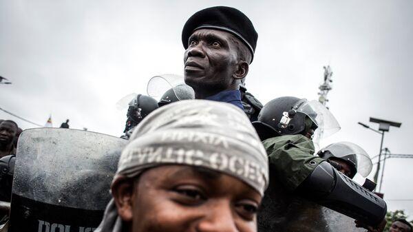 Полицейский охраняет сторонников Национального движения Конго Феликса Чисекеди и Виталия Камерхе на улице Киншаса