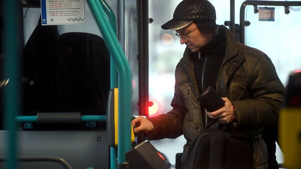 Пассажир оплачивает проезд в автобусе. Архивное фото
