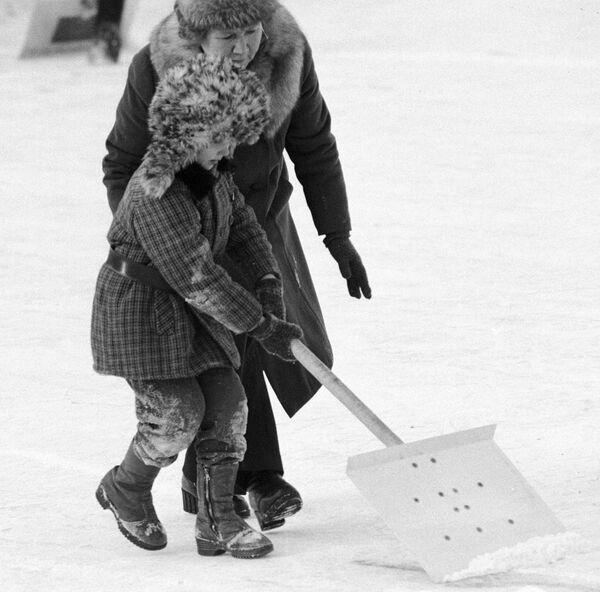 Ребенок убирает лопатой снег на катке