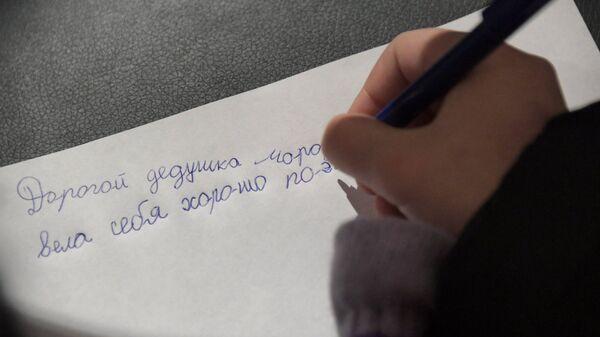 Ребенок пишет письмо Деду Морозу на почте в Московском зоопарке