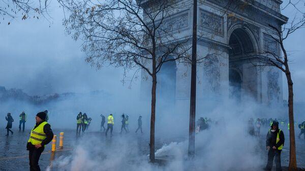 Участники протестной акции движения автомобилистов желтые жилеты, выступавшего с требованием снижения налогов на топливо, в районе Триумфальной арки в Париже. Архивное фото