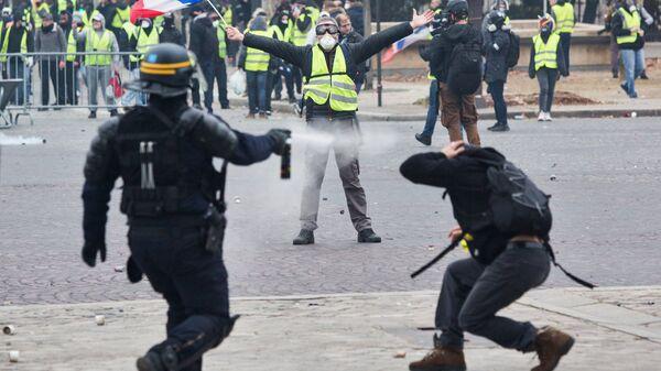 Сотрудник правоохранительных органов и активисты во время протестной акции движения желтые жилеты в Париже
