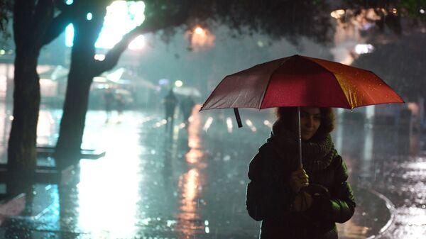 Девушка под зонтом на одной из улиц Ялты во время ливня