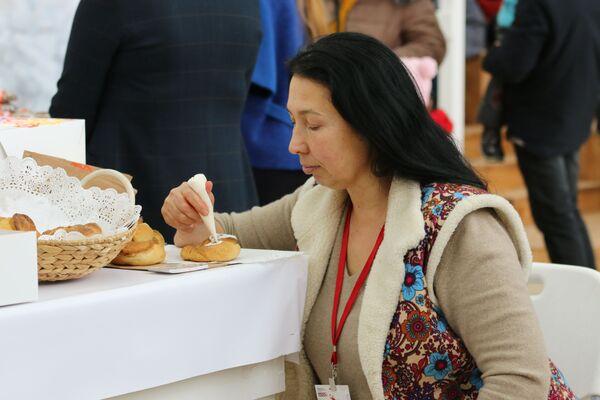 Мастерица вручную расписывает калачи на новогодней ярмарке в гостиной Деда Мороза в Тульском кремле