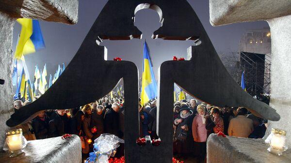 Люди зажигают свечи в день памяти жертв голодомора 1932-1933 годов на Украине