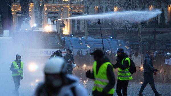 Полиция применяет водометы во время акции протеста желтые жилеты в Париже. 16 декабря 2018