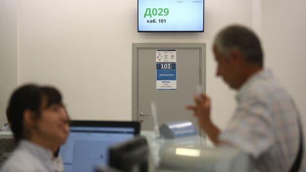 Кабинет дежурного врача, оснащенный табло электронной очереди, в городской поликлинике