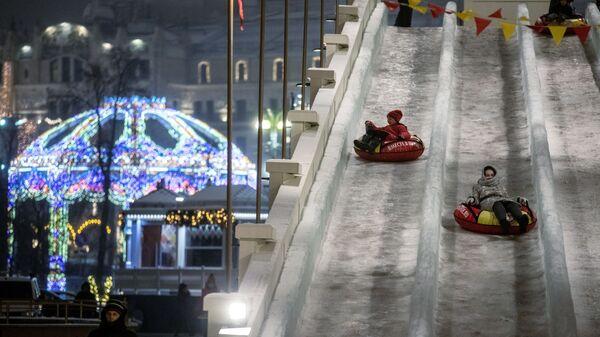 Дети катаются на ледяной горке на площади Революции в Москве