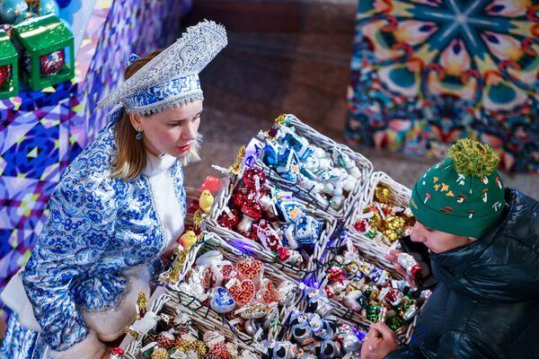 Покупатель выбирает елочные игрушки в торговом центре ГУМ в Москве