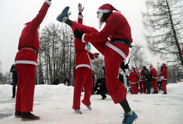 Участники благотворительного забега Дедов Морозов разминаются перед стартом на ВДНХ в Москве