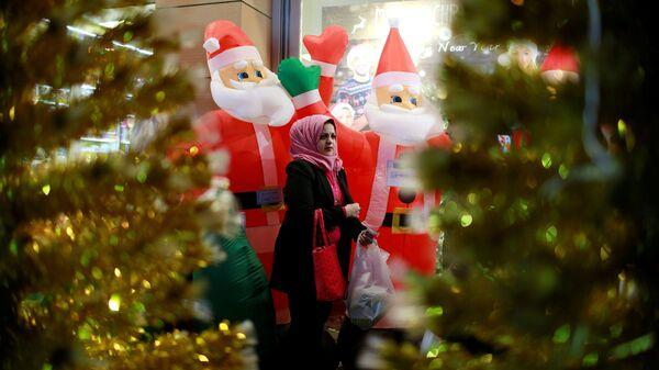 Женщина проходит мимо магазина, продающего рождественские украшения, в Багдаде, Ирак