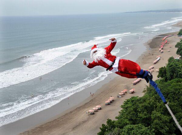 Банджи-джампер, одетый как Санта-Клаус, прыгает с платформы над пляжем в Куте, Бали