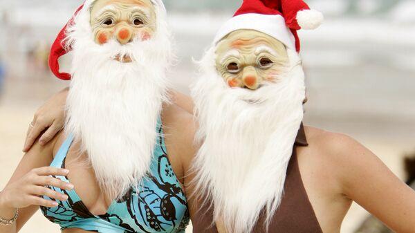 Британские туристы в масках и шляпах Санты Клауса на пляже Бонди в Сиднее