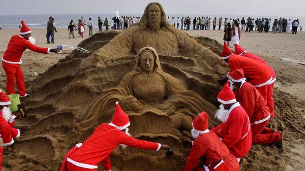 Художники в костюмах Санта Клауса создают песчаную скульптуру в канун Рождества на пляже города Пури, Индия