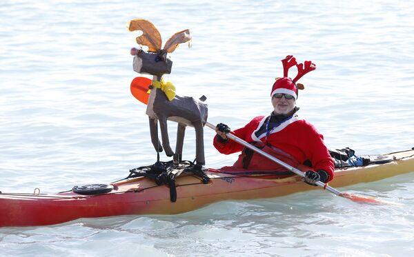 Мужчина в костюме Санта-Клауса на каноэ на пляже в центре Ниццы