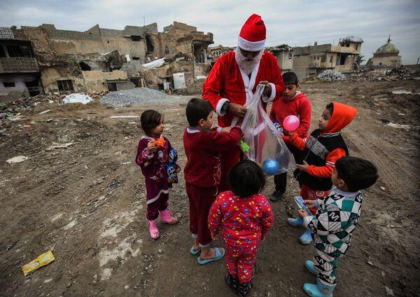 Мужчина, переодетый в Деда Мороза, раздает детям подарки на одной из улиц Мосула, Ирак