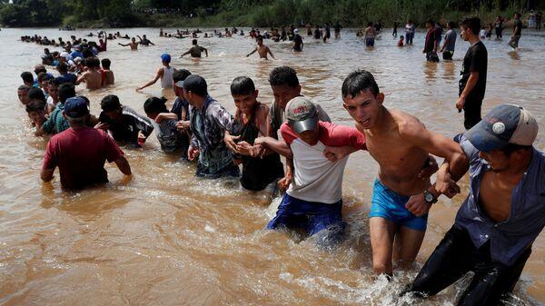 Мигранты, направляющиеся в США, пересекают реку на границе Гватемалы и Мексики