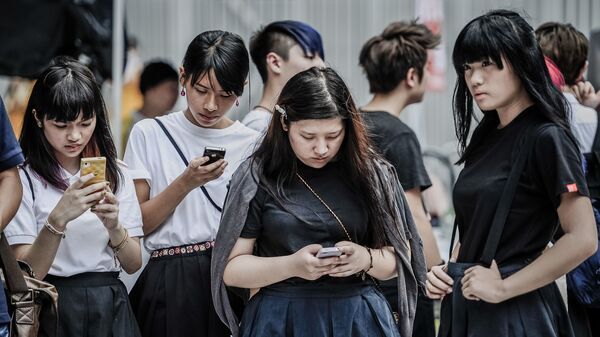 Жители Гонконга проверяют свои мобильные телефоны