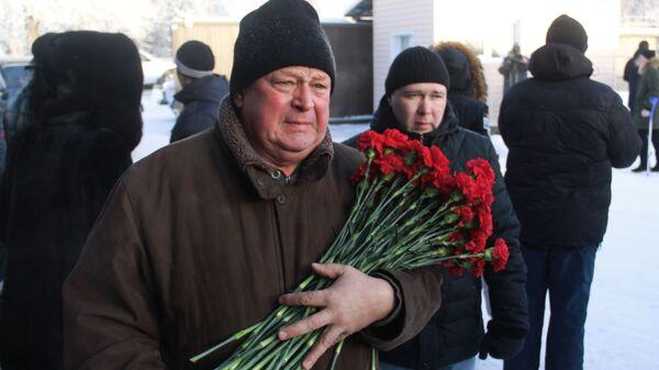 Мужчина с цветами перед началом похорон погибших при обрушении подъезда жилого дома в Магнитогорске. 4 января 2019