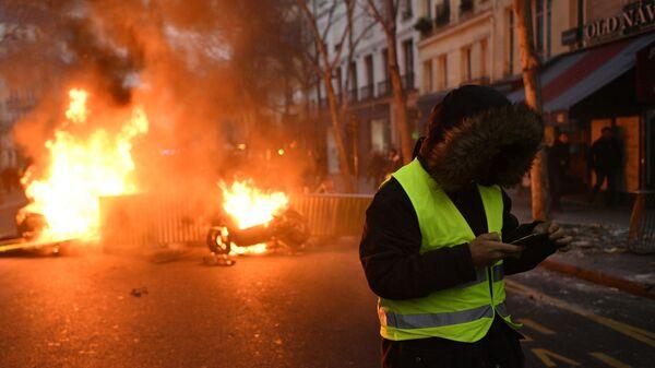 Участник протестной акции жёлтых жилетов недалеко от горящей баррикады на улице Парижа. 5 января 2018