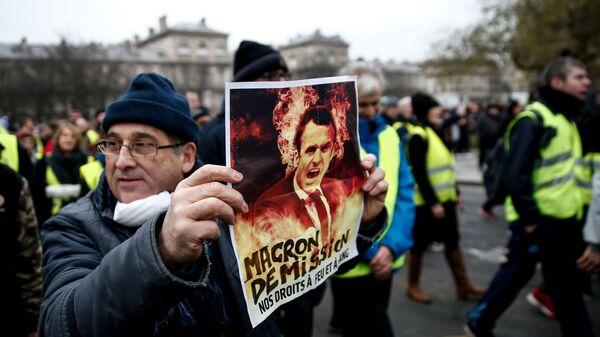 Демонстрант держит плакат во время акции желтых жилетов во Франции
