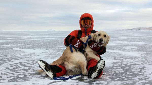 Турист с собакой на льду замерзшего озера Байкал