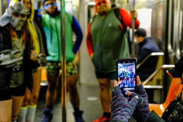 Пассажир фотографирует участников флешмоба В метро без штанов в вагоне поезда метро Нью-Йорка