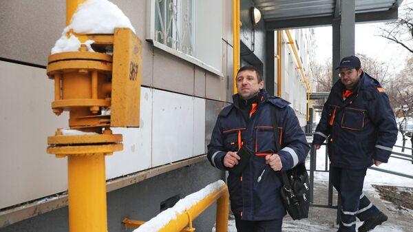 Сотрудники газовой службы подходят к газовой трубе для проверки