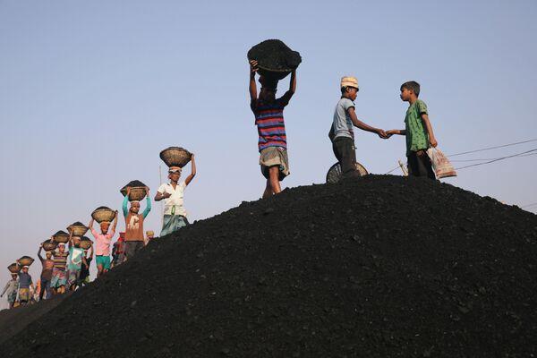Рабочие разгружают паром с углем в Дакке, Бангладеш