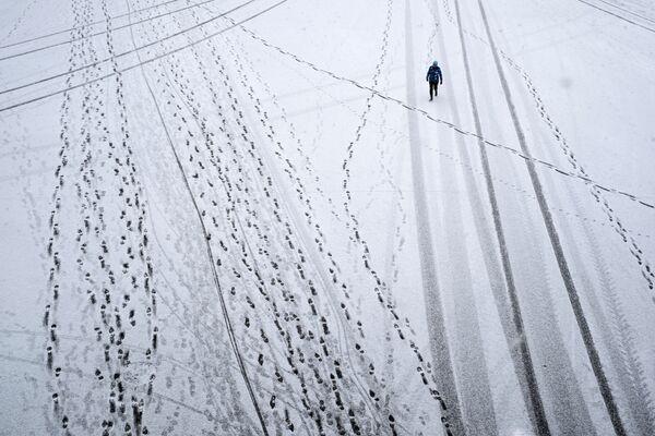 Прохожий во время снегопада в Парке Горького в Москве