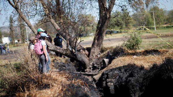 Местные жители наблюдают повреждения на месте взрыва незаконной врезки в газопровод в штате Идальго, Мексика. 21 января 2019