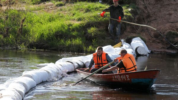 Сотрудники МЧС РФ выставляют боновые заграждения на одной из рек
