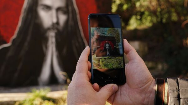 Мужчина фотографирует на смартфон граффити с изображением рэп-исполнителя Децла в Сочи