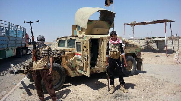 Боевики ИГ (запрещена в РФ) на контрольно-пропускном пункте в городе Байнджи, Ирак