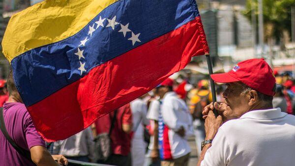 Мужчина с флагом Венесуэлы в Каракасе