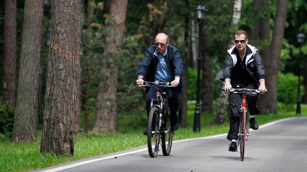 Президент РФ Дмитрий Медведев и председатель правительства РФ Владимир Путин катаются на велосипедах во время неформальной встречи в подмосковной резиденции Горки. 11 июня 2011 года